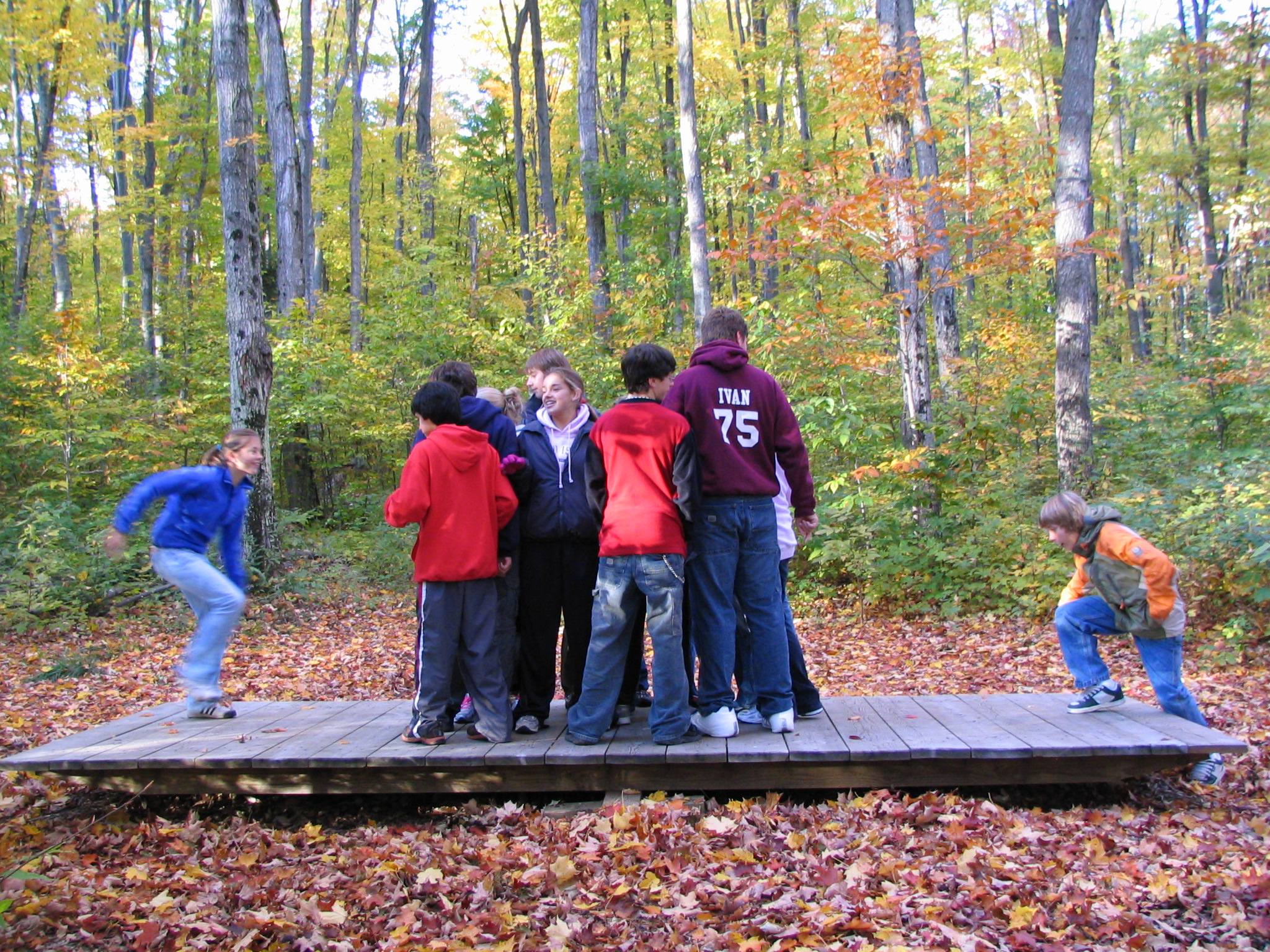 A group of students work to balance a giant teeter-totter.