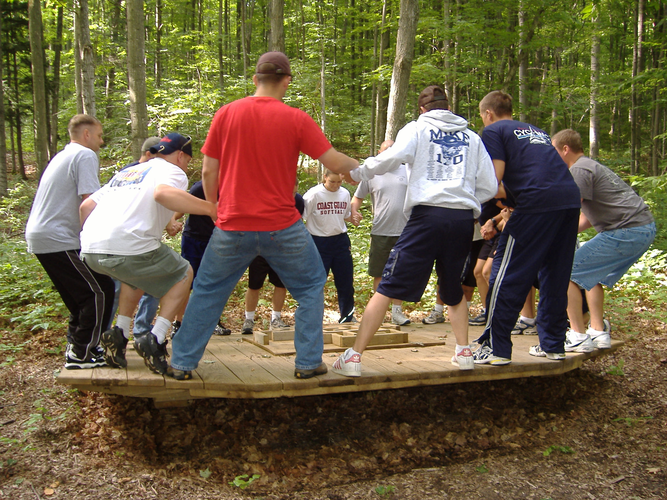 A group of adults stands on a low ropes course rocking board.