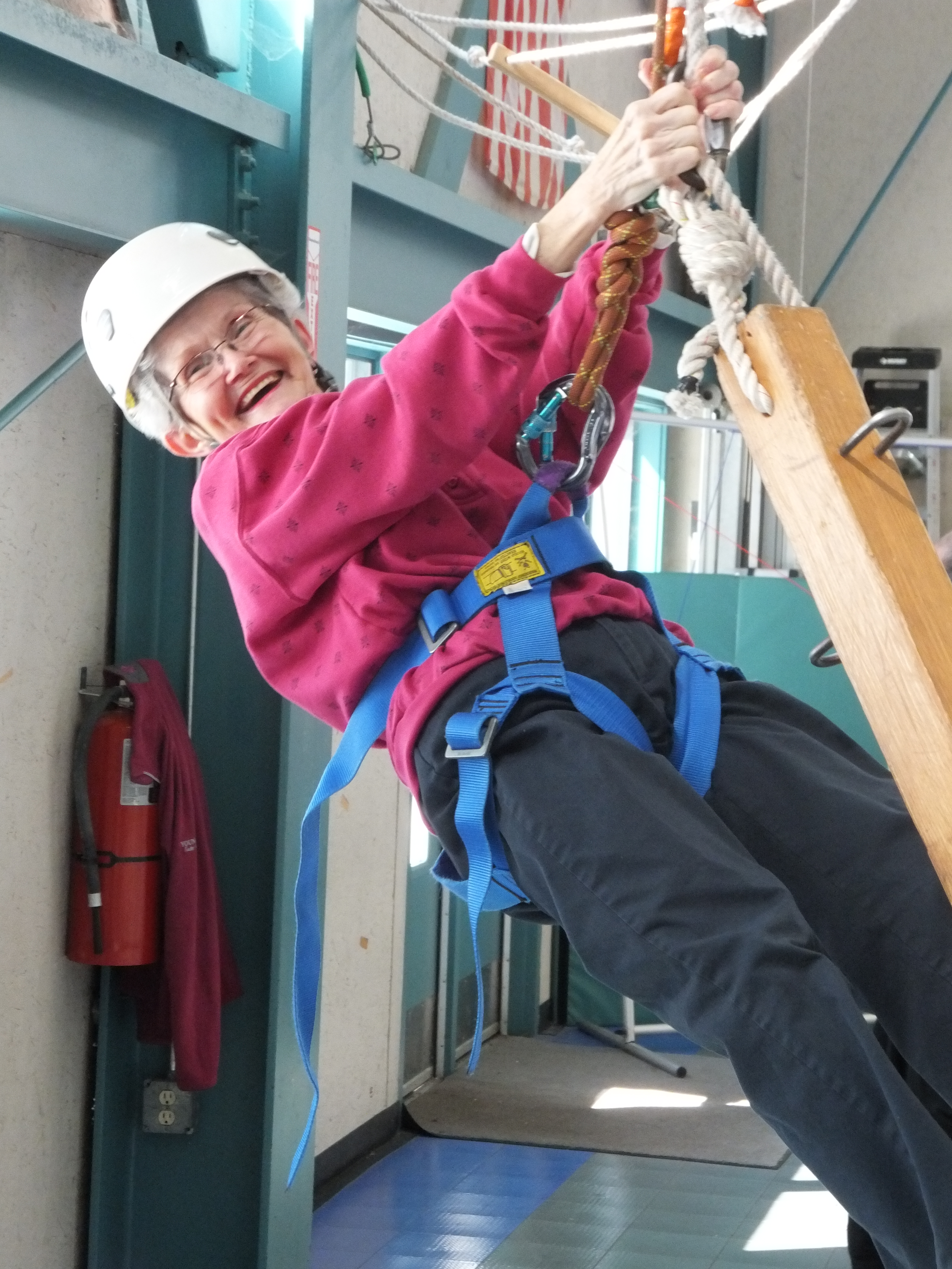 A woman climbs a high ropes course element.