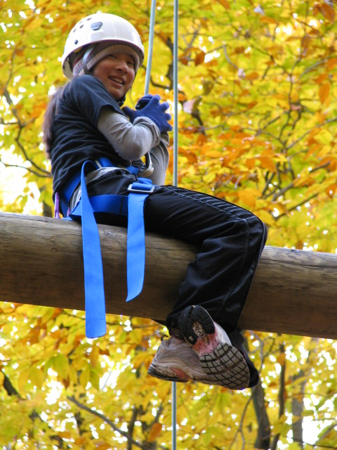 A climber sits on a beam on a high ropes course.
