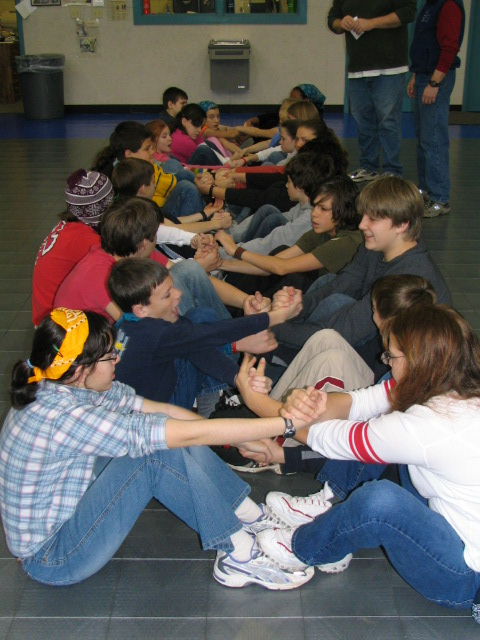 A group of students work to get everyone off the ground without using their hands.