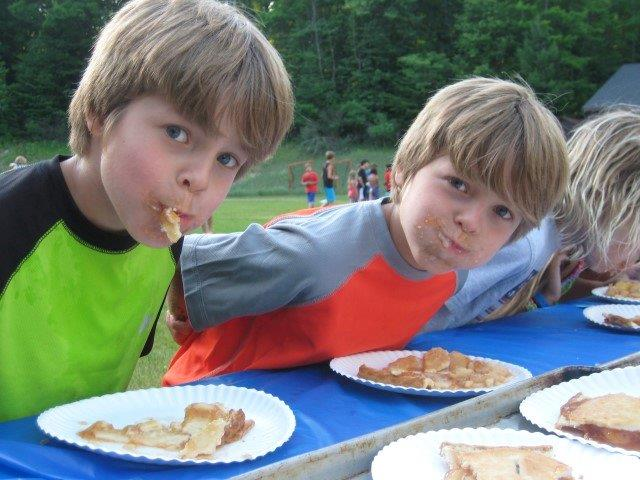 Two campers participate in a pie eating contest.