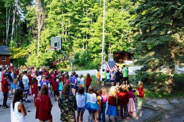 A group of campers look on, as the American Flag is raised.
