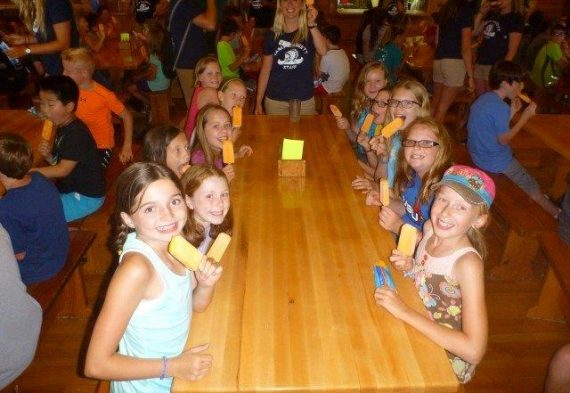 A group of campers enjoy a popsicle.