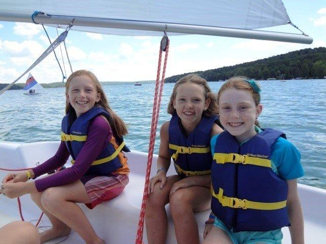 Three campers enjoy sailing a boat on Walloon Lake.